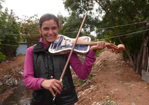 Tania, violinista de la Orquesta de Instrumentos Reciclados de Cateura, con uno de los instrumentos hechos a partir de residuos (Courtesy of Landfill Harmonic)